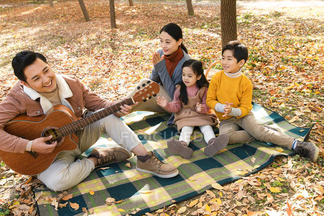 High angle view of smiling father playing guitar and happy family sitting on checkered plaid in park — Stock Photo