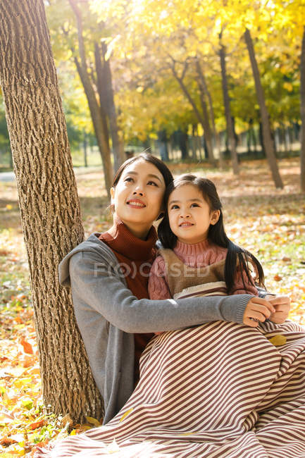 Beautiful happy asian mother and daughter sitting together and looking up in autumn park — Stock Photo