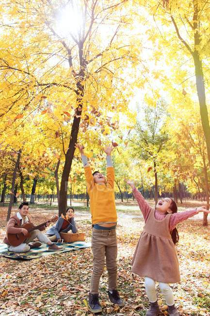 Happy kids playing with autumn leaves while parents resting on checkered plaid in park — Stock Photo