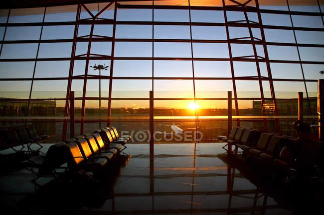 Vista de aviões através da janela do lounge do aeroporto vazio durante o pôr do sol — Fotografia de Stock