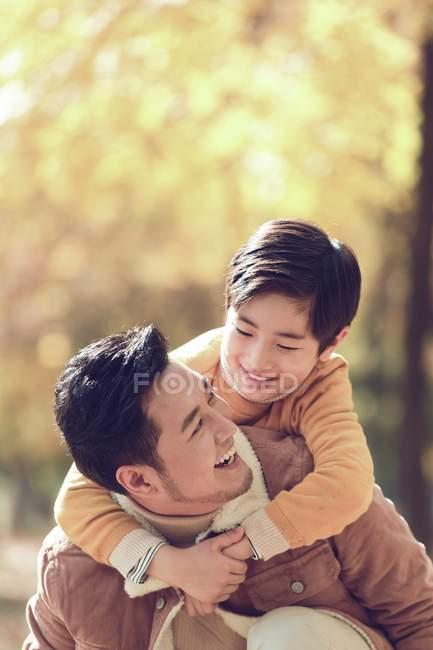 Щасливий молодий батько piggybacking чарівні усміхнений сина в Осінній Парк — стокове фото