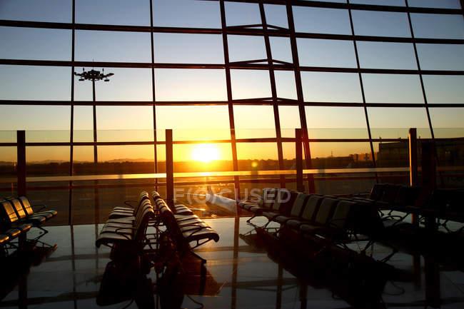Vista plana através da janela do lounge do aeroporto vazio durante o pôr do sol — Fotografia de Stock