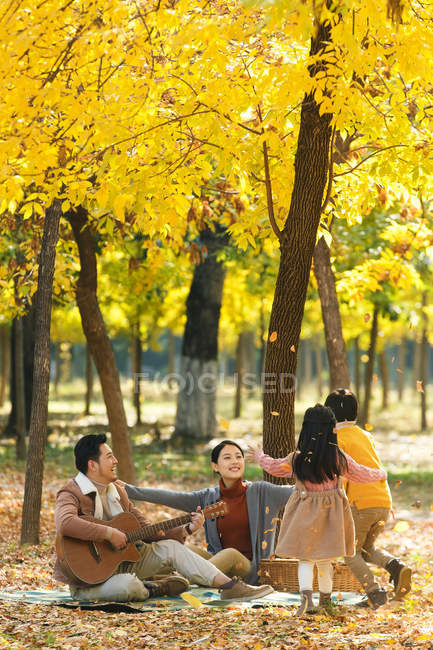 Happy young asian family with two children spending time together during picnic in park — Stock Photo