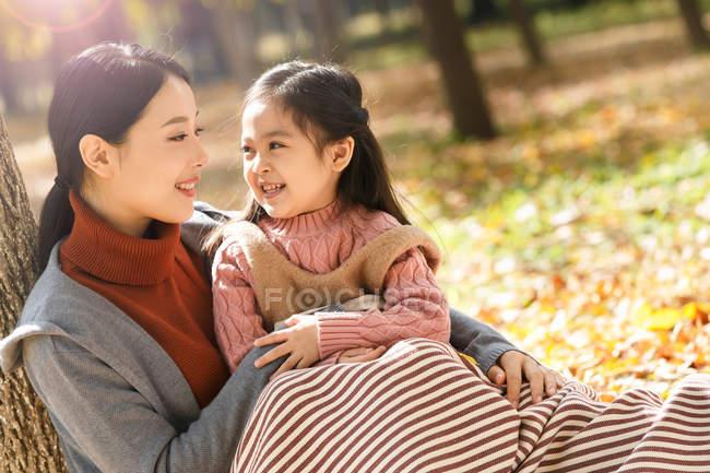 Hermosa asiático madre y hija mirando uno al otro mientras sentado juntos en otoño parque - foto de stock