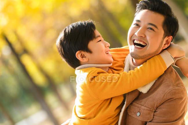 Heureux asiatique père et fils câlin dans automne parc — Photo de stock