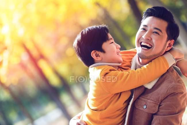 Feliz asiático padre y hijo abrazando en otoño parque - foto de stock