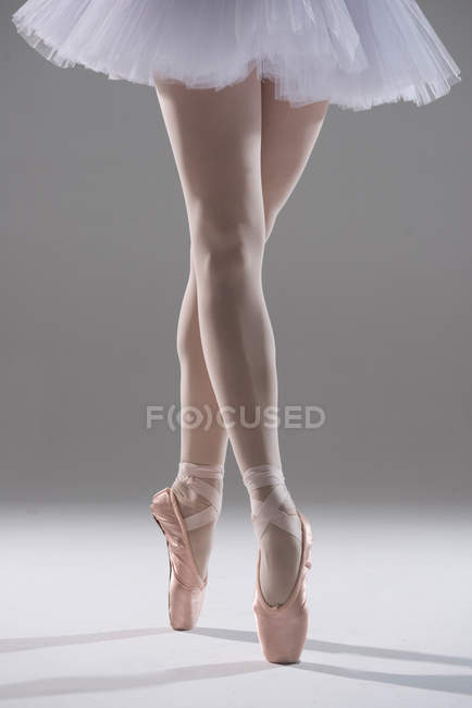 Cropped image of ballerina standing in pointe shoes on grey background — Stock Photo