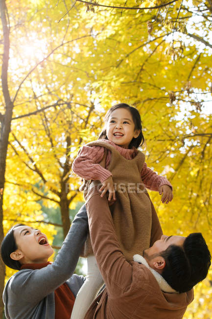 Happy asian parents lifting daughter in autumnal park — Stock Photo