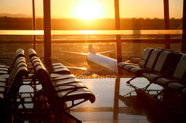 Blick durch das Fenster aus der leeren Flughafenlounge bei Sonnenuntergang — Stockfoto