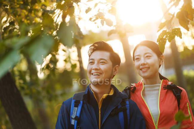 Felice giovane coppia asiatica con gli zaini guardando lontano nel parco — Foto stock