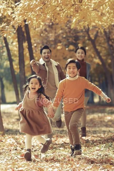 Felici giovani genitori e bambini carini che corrono nella foresta autunnale e sorridono alla macchina fotografica — Foto stock