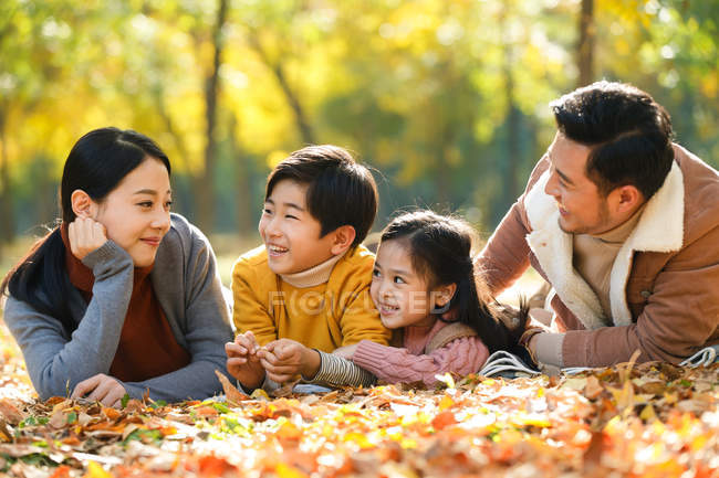 Happy young parents with two kids lying together and smiling each other in autumn park — Stock Photo