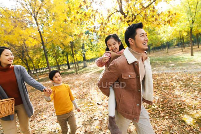 Счастливая молодая семья с двумя детьми гуляет вместе в осеннем парке — стоковое фото