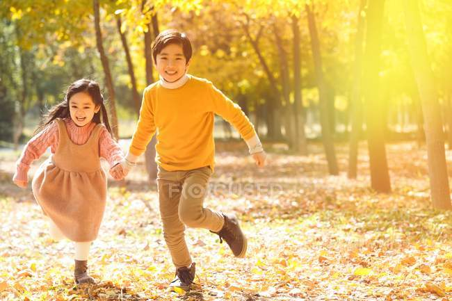 Adorable happy asian children running together in autumn forest — Stock Photo