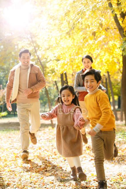 Щасливі батьки молодих і милі діти працює в осінньому лісі — стокове фото