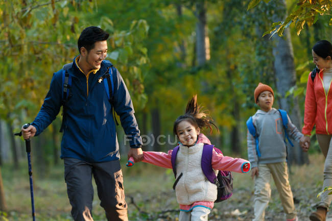 Happy young asian family with backpacks hiking together in forest — Stock Photo