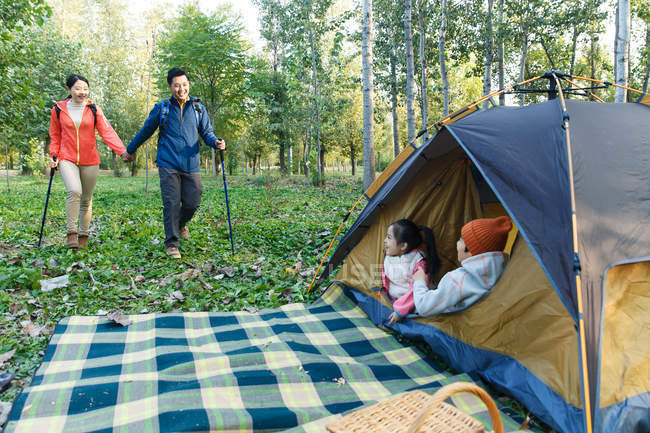 Adorable kids sitting in tent and smiling parents walking with trekking sticks in forest — Stock Photo