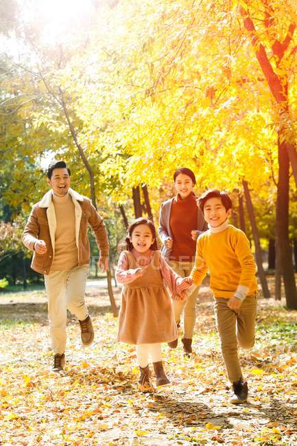 Happy young parents and cute kids running in autumn forest and smiling at camera — Stock Photo