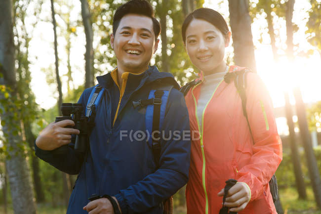 Happy young asian couple with binoculars and trekking sticks smiling at camera in forest — Stock Photo