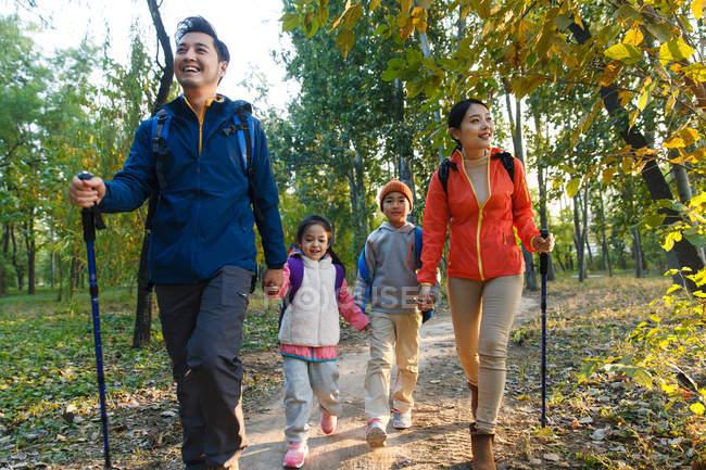 Heureux jeune asiatique famille avec sacs à dos et trekking bâtons marcher ensemble dans automne forêt — Photo de stock