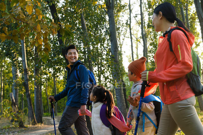 Side view of happy young asian family with backpacks and trekking sticks walking together in autumn forest — Stock Photo