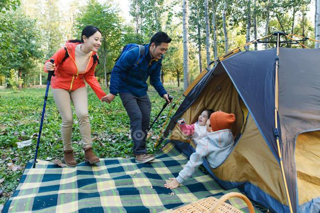 Parents heureux avec des bâtons de randonnée regardant adorables enfants au repos sous la tente dans la forêt — Photo de stock