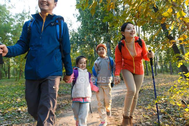 Feliz jovem asiático família com mochilas e trekking varas andando juntos no outono floresta — Fotografia de Stock