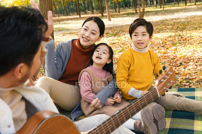 Cropped shot of father playing guitar and happy family sitting on plaid in autumn park — Stock Photo
