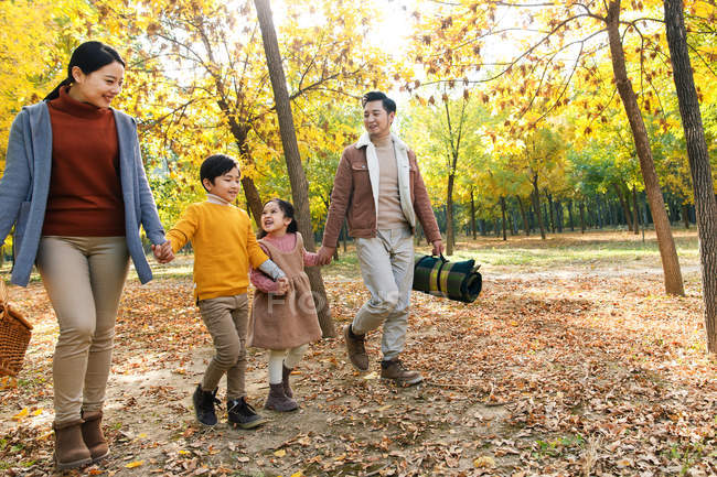 Happy family with picnic basket holding hands and walking in autumn forest — Stock Photo