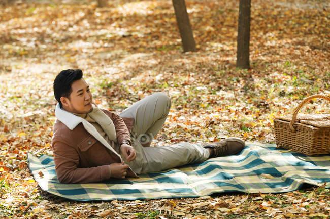 Schöner asiatischer Mann liegend auf Decke im herbstlichen park — Stockfoto