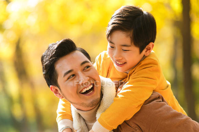 Happy young father piggybacking adorable smiling son in autumn park — Stock Photo