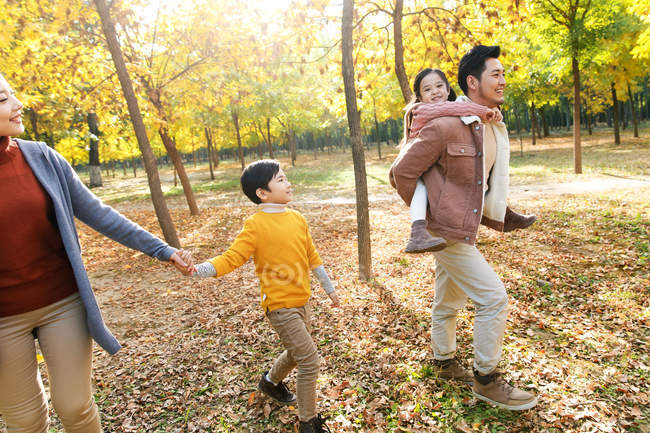 Feliz jovem asiático família andando juntos no outono floresta — Fotografia de Stock