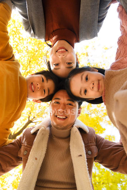 Bottom view of happy young asian family with two kids standing together and smiling at camera in autumn forest — Stock Photo