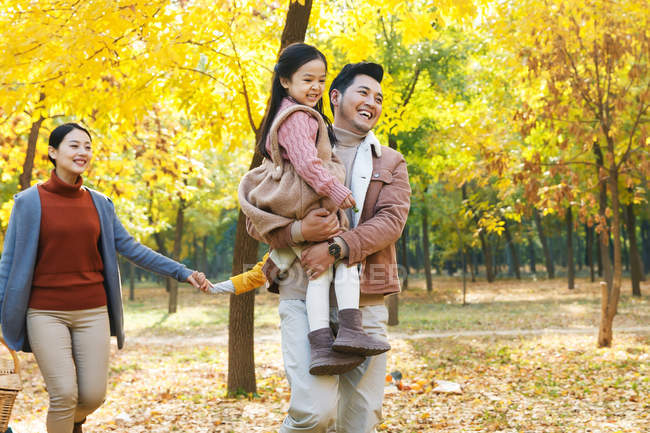 Happy young asian family with two children walking together in autumn forest — Stock Photo