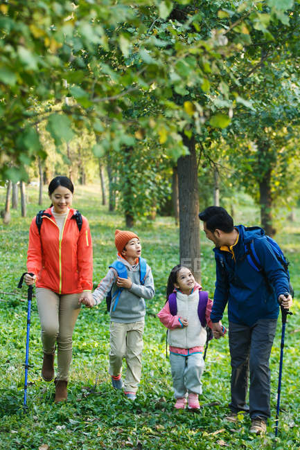 Happy young family with backpacks and trekking sticks walking in forest — Stock Photo