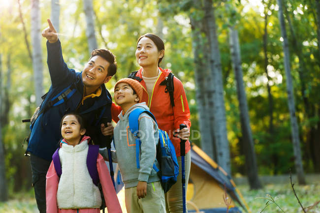 Happy asian family with backpacks trekking together in autumn forest — Stock Photo