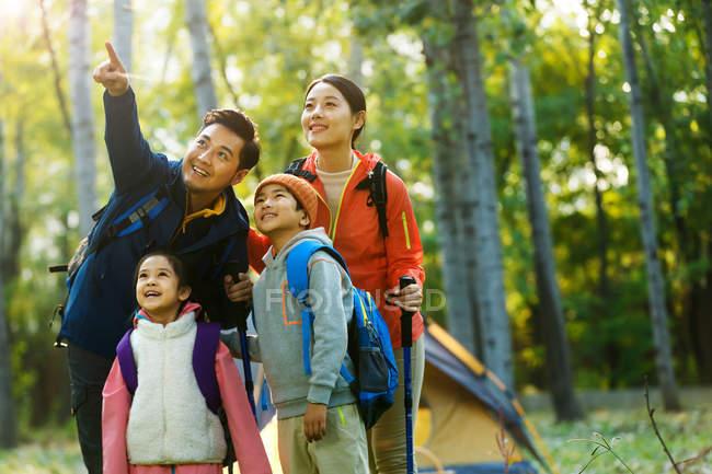 Feliz familia asiática con mochilas trekking juntos en el bosque del otoño - foto de stock