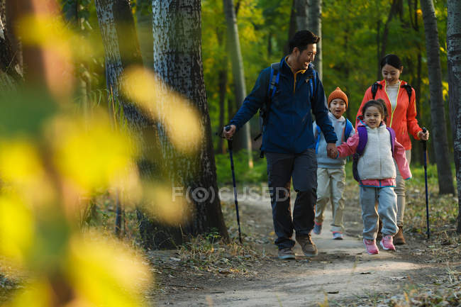 Selective focus of happy young family with backpacks and trekking sticks walking together in forest — Stock Photo