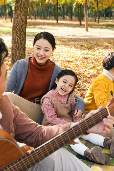 Happy family looking at father playing guitar in autumn park, cropped shot — Stock Photo
