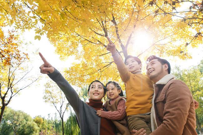Vista a basso angolo di genitori felici che trasportano bambini e che indicano nel parco autunnale — Foto stock
