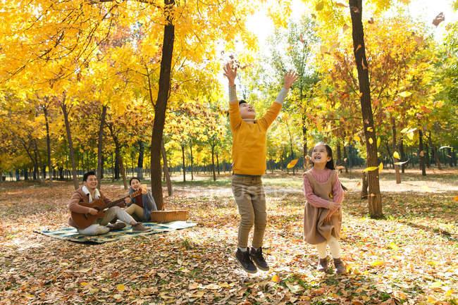 Niños felices jugando con hojas de otoño mientras los padres descansan en cuadros a cuadros en el parque - foto de stock