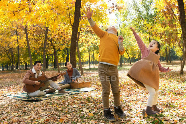 Adorable happy kids playing with autumn leaves while parents sitting with guitar behind in park — Stock Photo