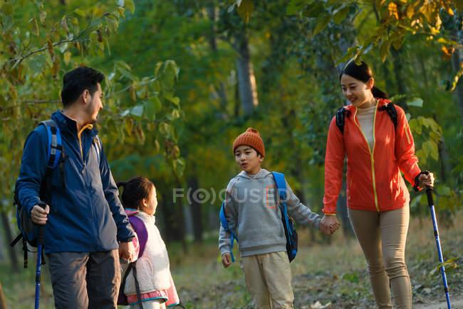 Heureux jeune asiatique famille avec sacs à dos et trekking bâtons randonnée ensemble dans forêt — Photo de stock