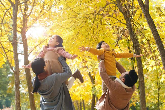 Счастливые молодые родители с очаровательными детьми в осеннем парке — стоковое фото