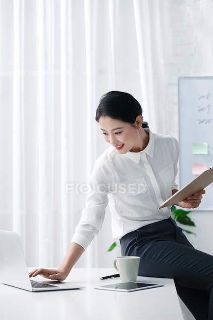 Attractive asian businesswoman sitting on table and using laptop in light office — Stock Photo