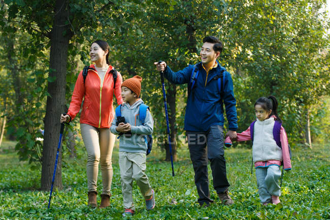 Happy young asian family with backpacks and trekking sticks walking together in forest — Stock Photo