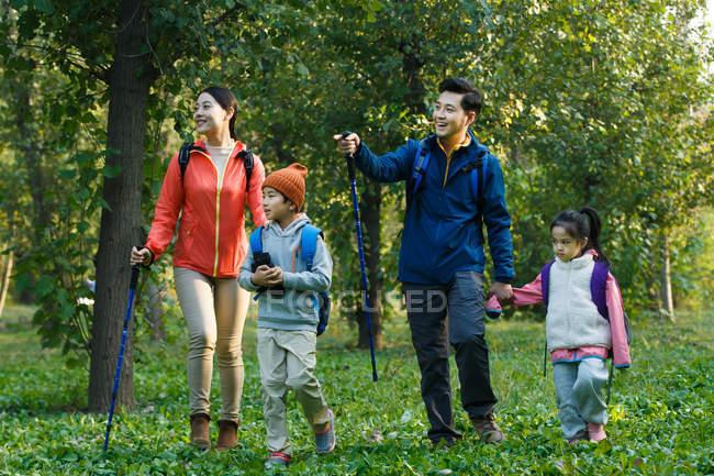 Feliz família asiática jovens com mochilas e trekking varas andando juntos na floresta — Fotografia de Stock