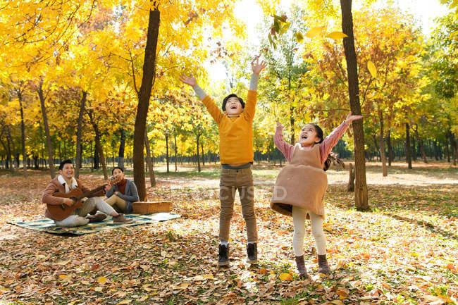 Crianças felizes brincando com folhas de outono, enquanto os pais descansam em xadrez xadrez no parque — Fotografia de Stock