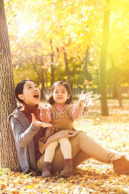 Happy asian mother and daughter sitting near tree and playing with leaves in park — Stock Photo