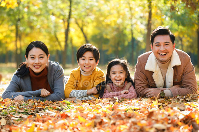 Heureux jeunes parents avec deux enfants couchés ensemble et souriant à la caméra dans le parc d'automne — Photo de stock